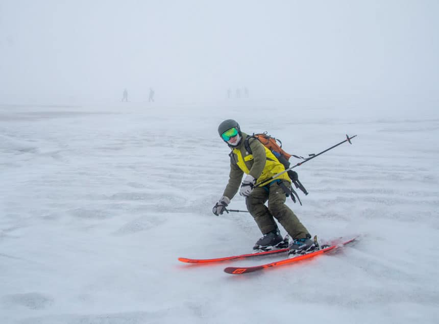 Skiier in green & yellow outerwear, green reflective goggles & olive helmet goes skiing in antarctica down a snowfield on a foggy day with bright orange skis & silver ski poles.