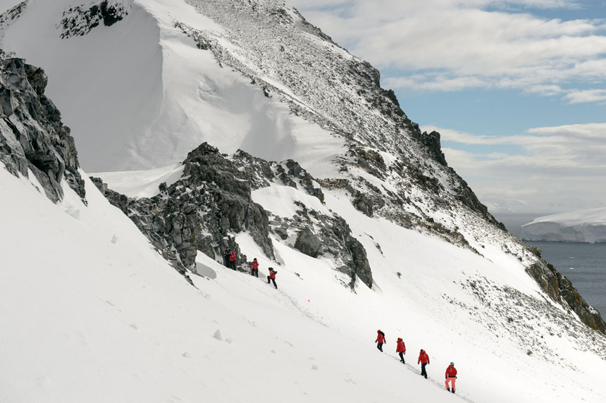 polar travelers in red jackets go trekking in antartica uphill toward a rock band, high above the water, on a sunny day.