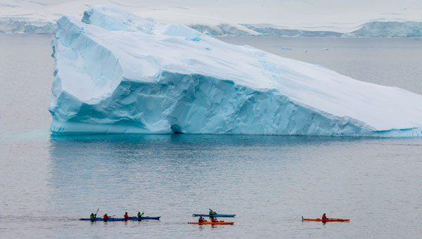 Group of kayakers paddles past an enormous iceberg in calm seas on an Antarctica trip.