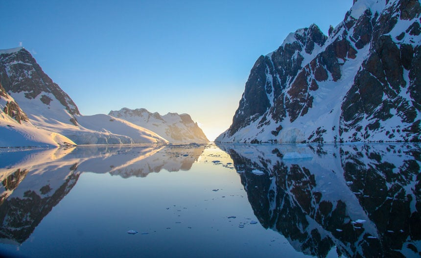 Sun rises between 2 snow-covered, rocky mountain ranges with glassy water between them. An answer to what is so special about Antarctica.