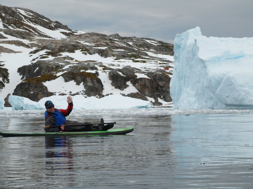 Man lays down & waves from atop a bacl & green stand-up paddleboard while floating in calm water beside an iceberg in antarctica.