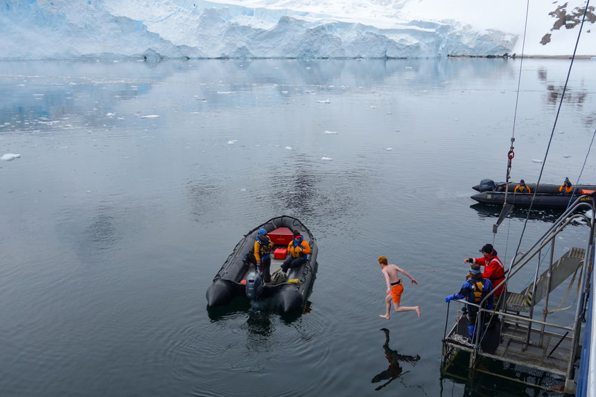 Red-headed man in orange swim trunks jumps off water-level platform into freezing antarctica waters with snow field in background & 2 black Zodiacs with brightly-dressed guides watching.