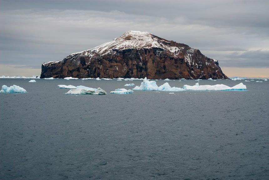 View approaching Paulet Island, a place in Antarctica, with its volcanic crater in the center, brown cliff walls & ocean with small icebergs floating out front.