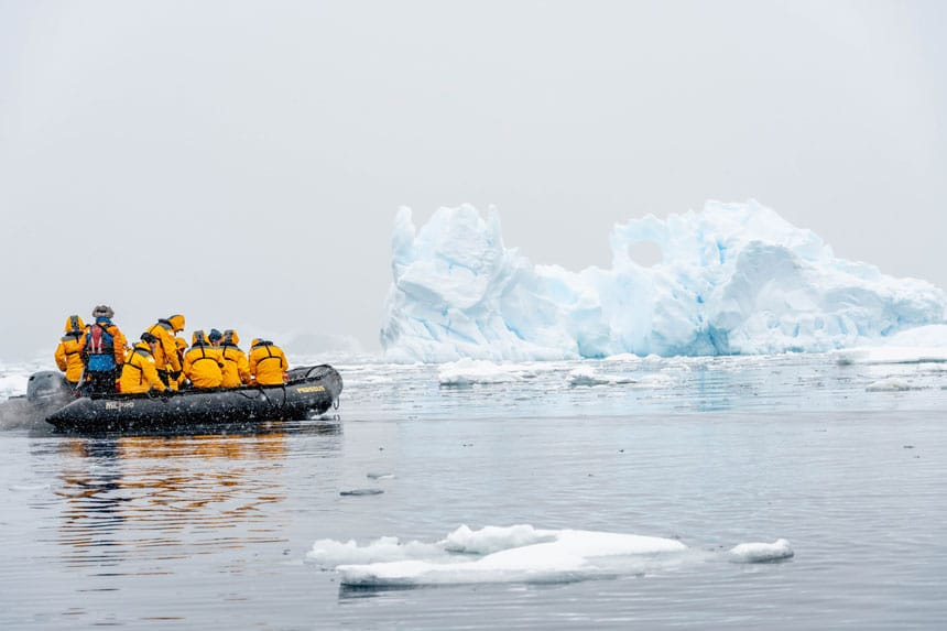 Group of Antarctica travelers in yellow jackets sits in a black Zodiac boat while cruising past a white iceberg on a snowy day.