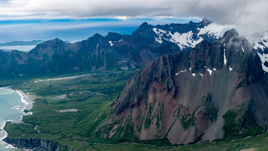 Aerial view of volcanic Aleutian Islands travel, with blue sky & sea, verdant green shores & jagged peaks.