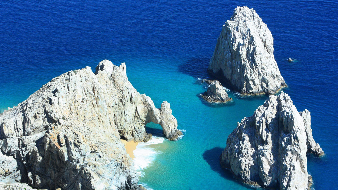 Aerial view of large white basalt rocks rising up out of calm deep blue & turquoise waters on a sunny day in Baja California.