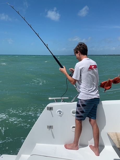 A boy stands on the back of a white catamaran holding a fishing pole for a fishing activity during a Belize charter vacation.