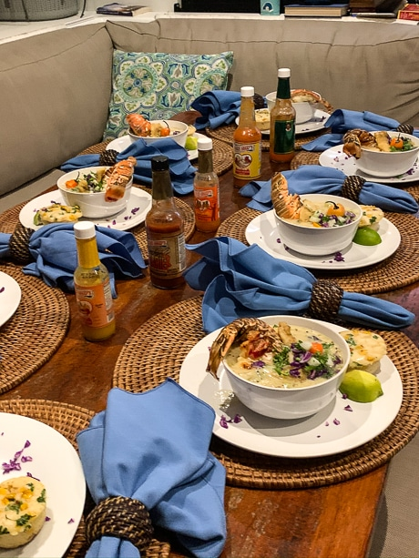 A wooden table with 8 dinner plates of lobster soup, set with 5 hot sauce bottles and bright blue napkins.