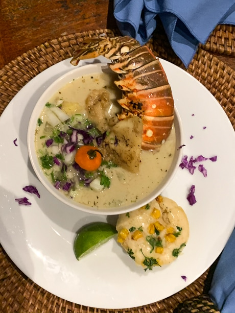 A bowl of soup topped with vegetables and a whole fresh lobster sits on a white plate with a corn patty and line wedge.