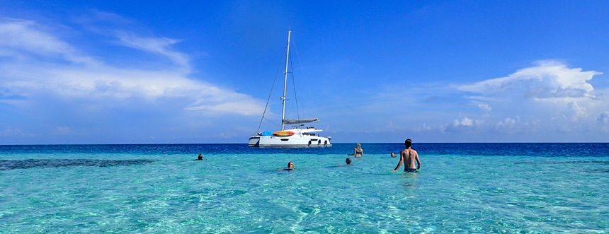 On a bright sunny blue sky day a group of people swim around a white Belize sailboat that floats on the teal blue ocean horizon.