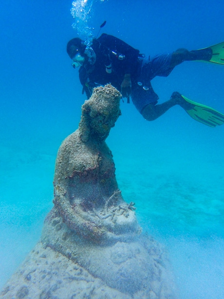 In crystal clear blue water a scuba diver swims by a submerged underwater statue in Belize.