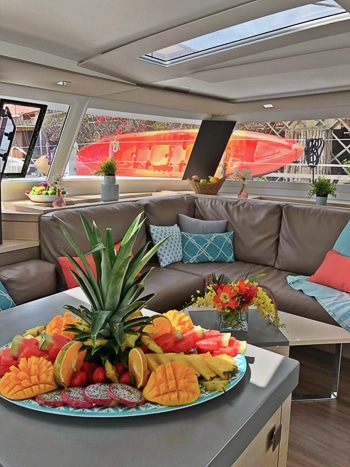 Indoor lounge area aboard Belize catamaran. Upholstered bench seating around a coffee table and a kitchen islands with a plate fresh fruit.