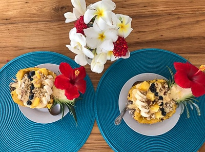 Cuisine aboard Belize sailboat charter, a cut open half yellow pineapple filled with yogurt, granola and other cut fruit.
