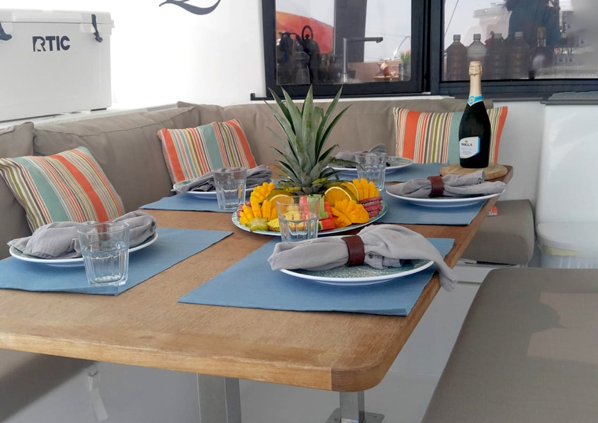 Outdoor marine dining table and seating area aboard a Belize catamaran. Table is set for 5 people with a plater of fresh fruit in the middle.