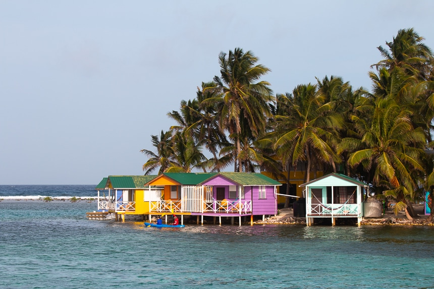 Brightly pained houses on stilts hover over the ocean water on the shoreline of a palm tree filled island called tobacco Caye in Belize.