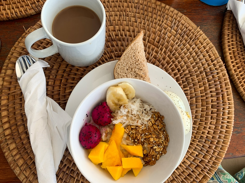 Breakfast of granola, coconut shavings, and brightly colored fresh fruit over yogurt in a white bowl with a slide of bread and a cup of coffee.