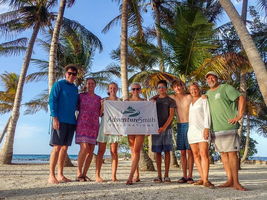 Two families pose together on a sandy palm tree filled island in Belize and hold the AdventureSmith Explorations Flag.