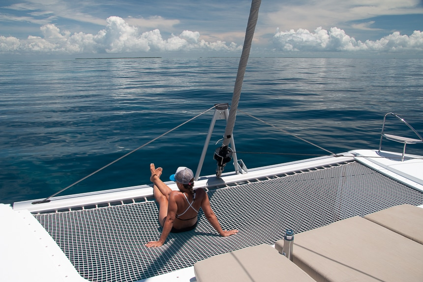 A woman in a bathing suit sits on the netted trampoline at the back of a Belize catamaran looking out over the dark blue ocean.