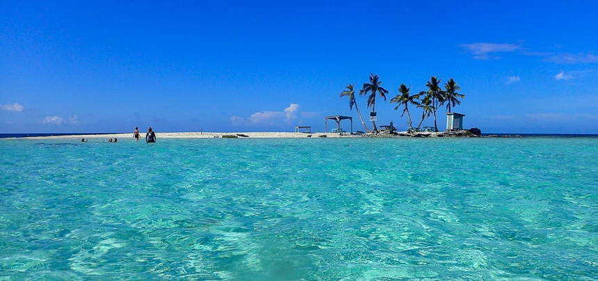 I n Belize a tiny island of sand an palm trees divides the photo with a cloudless blue sky above and crystal teal water below