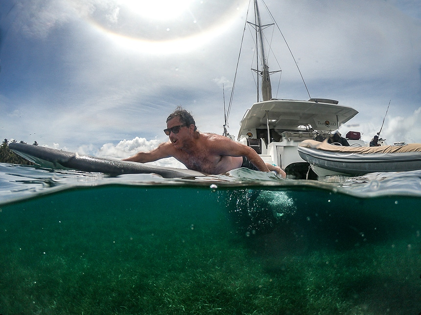 A above and below water photo showing a man paddling a surfboard away from a white catamaran floating in the ocean of Belize.