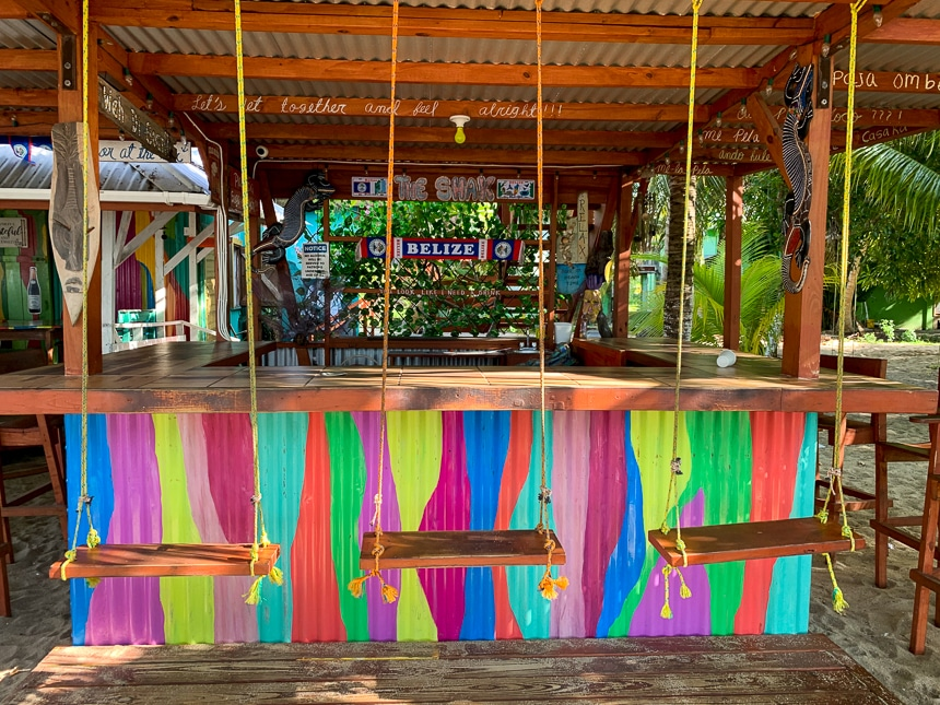 An ocean front brightly colored open air bar with swings as seats found in Plascencia in Belize.