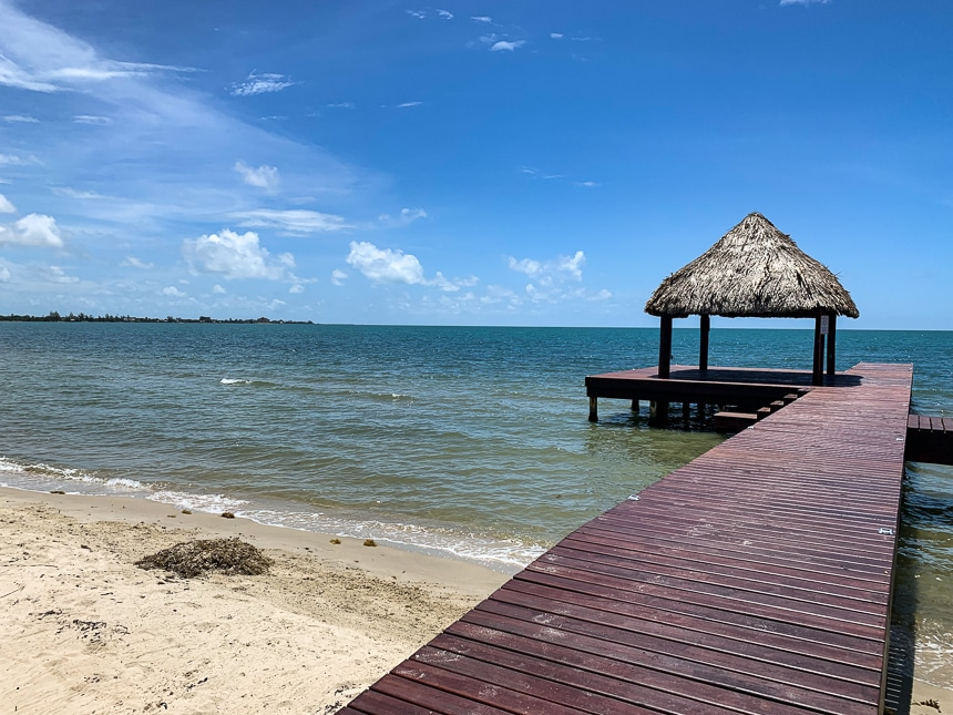 A dark red wooden dock extends into the blue ocean from the sandy shore in Belize, with a thatch roof cabana at the end.