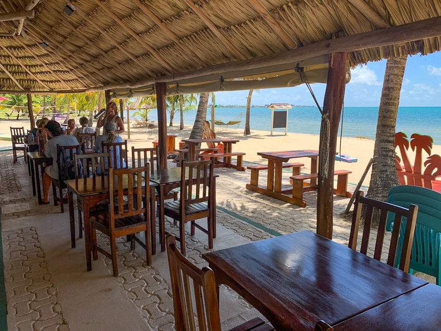 An open air and ocean front restaurant with a thatch roof and wooden tables and chairs shown on bright sunny day on an island in Belize.
