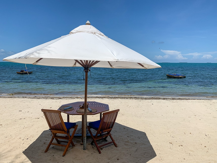In Belize a small table for two is under a large white umbrella set on the beach with views of the blue teal ocean and sky.