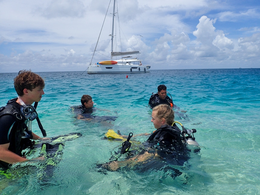 In Belize a group of scuba divers float in shallow water during their training in front of their private catamaran charter boat