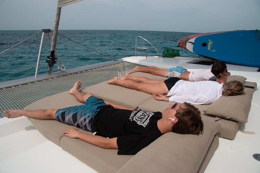 three travelers lay on tan lounge mats at the back of a white Belize catamaran as it sails through the ocean on a overcast day.