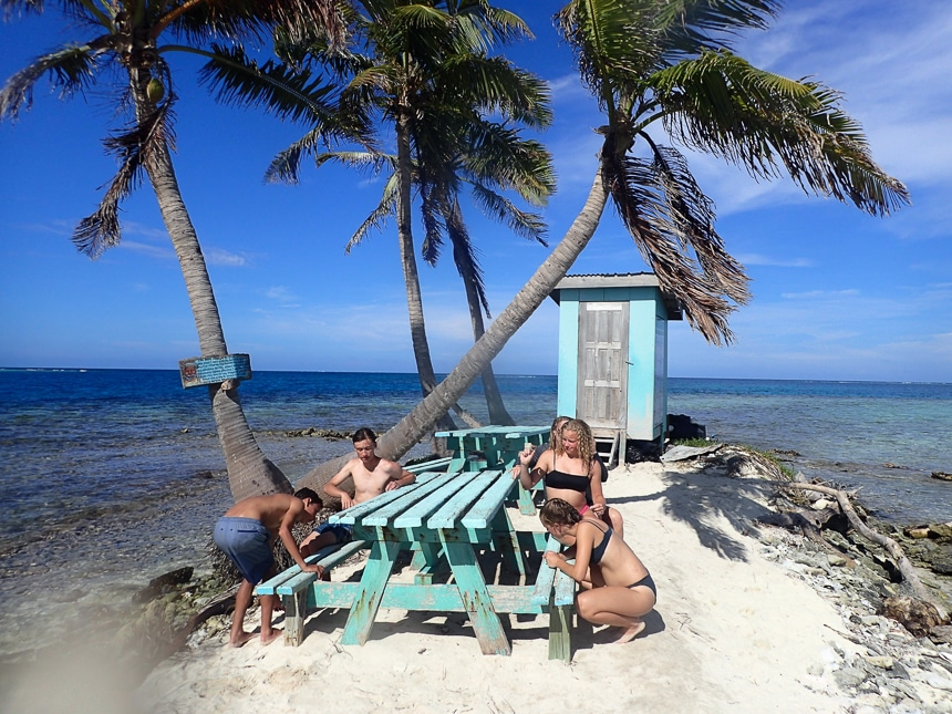 Children in bathing suits sits around teal wooden picnic tables on a tiny sandy islands of palm trees during a Belize vacation.