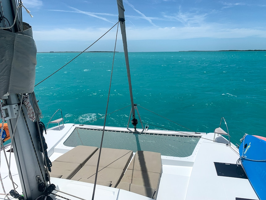 Looking over teal ocean water and blue sky from the back of a white Belize catamaran with three lounge mats and a netted trampoline.