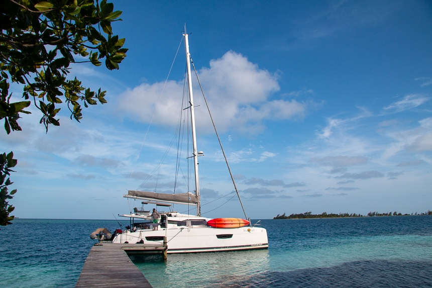 A wooden dock stretches into the teal blue ocean water of Belize, a bright while sailboat floats at the end waiting for its guests.