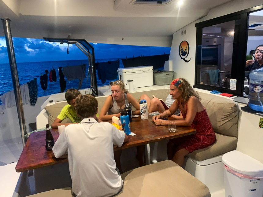 Four people sit around the outside dining table of a Belize sailboat playing games as the sun sets in the distance.
