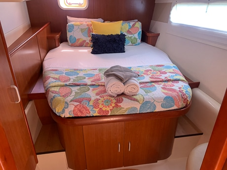 Inside a cabin aboard a Belize sailboat. One long window, a wooden bedframe with cabinets sits underneath a mattress wrapped in colorful blankets.