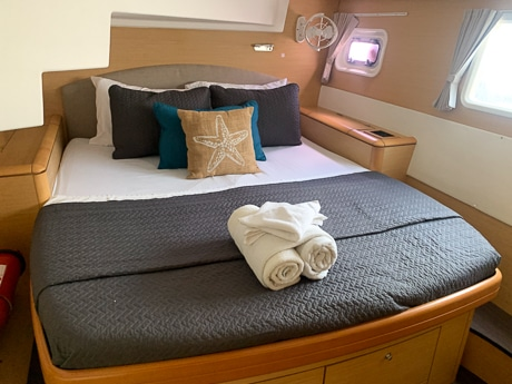 A windowed cabin aboard a Belize sailboat. Includes a wooden bedframe with cabinets underneath a mattress wrapped in a blue blanket and rolled towels on the end.