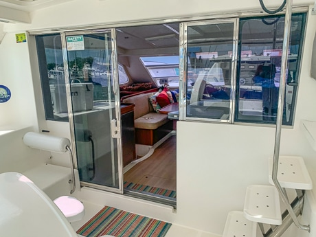 From outside on the back deck of a Belize catamaran looking through sliding glass doors at the inside dining salon.