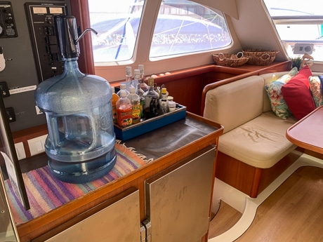 The indoor salon dining area aboard a Belize sailboat. Upholstered bench seating around a table with a large waters jug and tray of condiments on the counter.