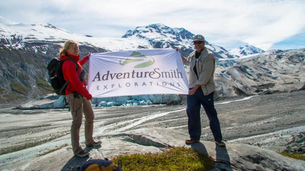 Two travelers holding an AdventureSmith Explorations flag in front of Kenai Fjords glaciers on a Denali vacation