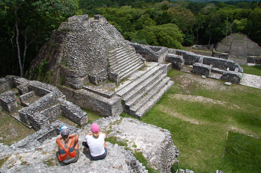 Two female travelers sit and look down over a set of stone Mayan temple ruins in Belize surrounded by green lush jungle.