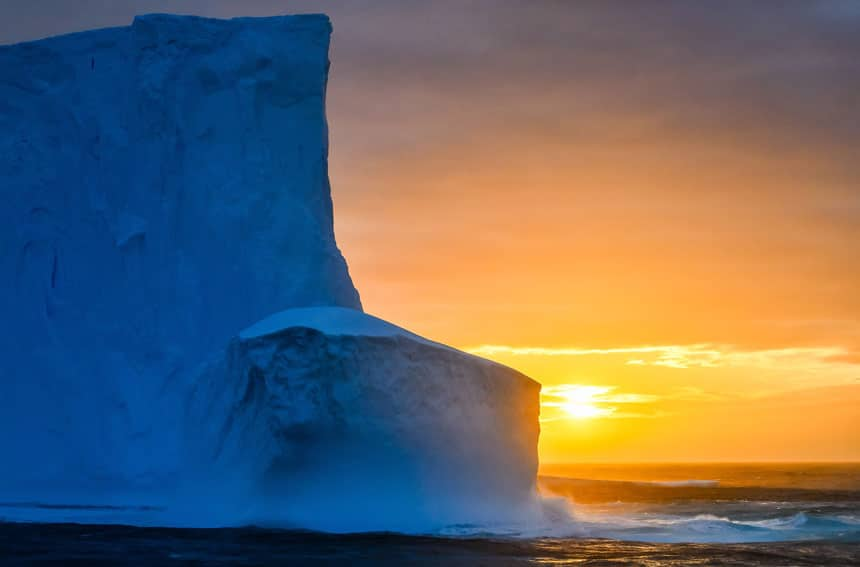 Sun sets behind a very tall blue shelf of ice known as the Ross Ice Shelf, one of the places to visit in Antarctica.