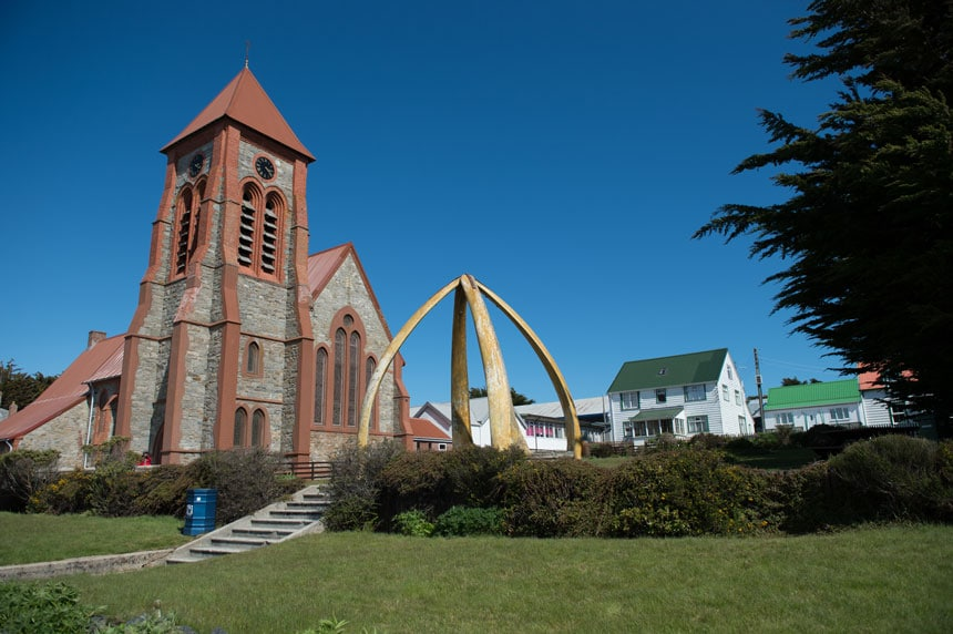 Stone church with brick-red trim surrounded by green grass & hedges, white houses with green roofs & an orb-like gold arch, on a sunny day in Port Stanley, Falklands.