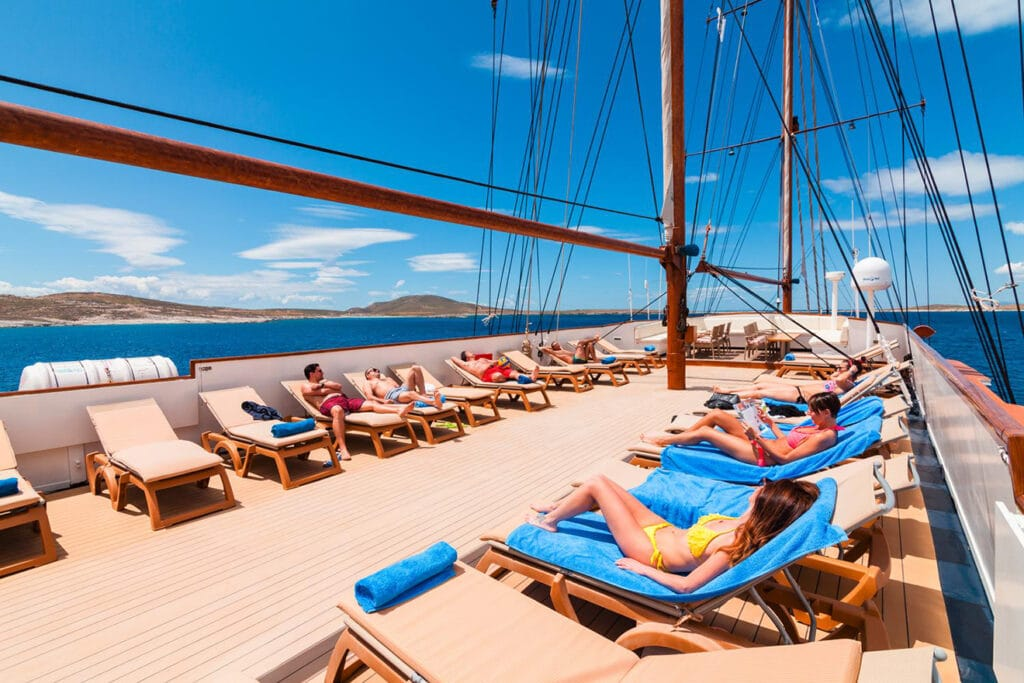 Travelers in bathing suits sunbathe in lounge chairs on a Mediterranean yacht charter sailboat under the sail lines.