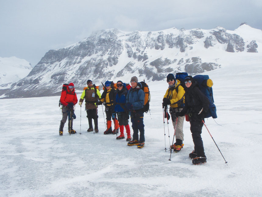 Group of polar travelers with large packs & trekking poles stand atop a snowfield during the Shackleton Crossing on South Georgia Island.