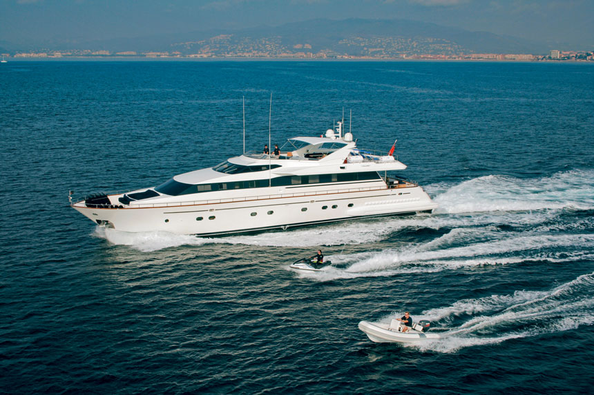Private white yacht cruises in open Mediterranean waters with jet ski & tender cruising beside.