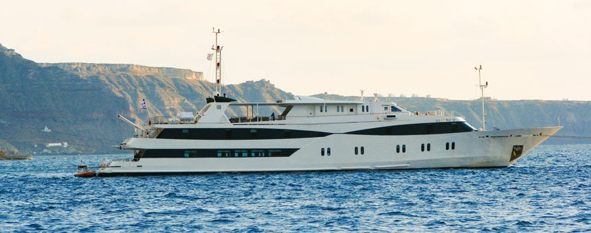 Large white & black yacht sits in blue water beside a large cliffed island.