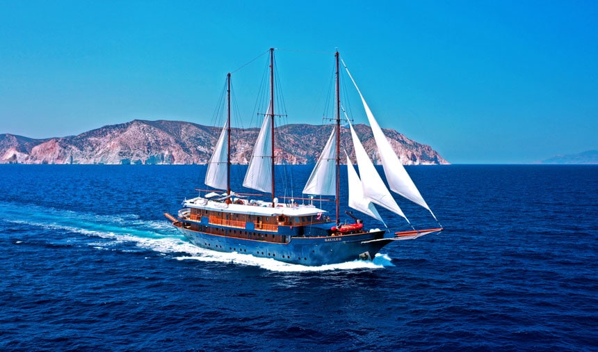 Classic motorsailor with white sails, wooden upper deck & blue hull cruises in open water beside Mediterranean islands.