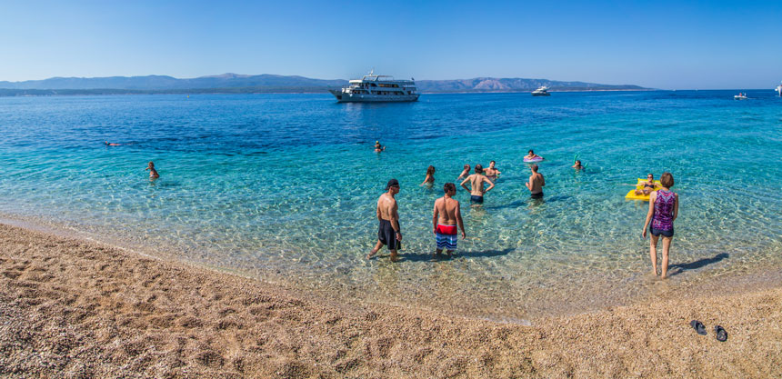 Swimmers in turquoise water with a small ship in the background & a white-sand beach in the foreground, on a sunny day in the Mediterranean.
