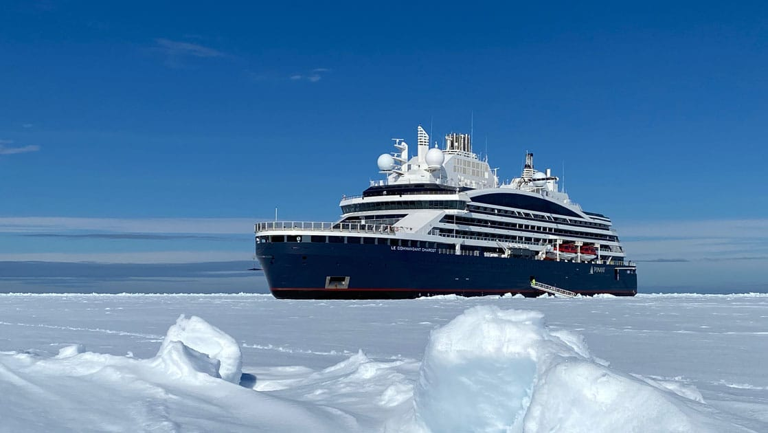 Expedition ship with dark blue hull & white upper decks sits in ice during Le Commandant Charcot Northeast Greenland Voyages.
