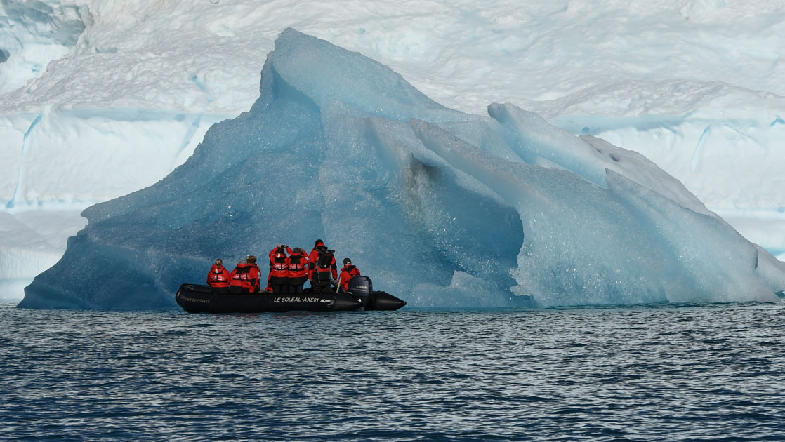 Zodiac with travelers in red jackets cruises by a large iceberg during cruises to Iceland and Greenland aboard Le Commandant Charcot.